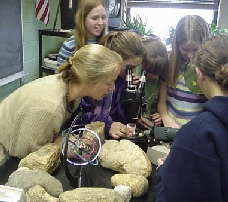 Photograph of middle school students using a microscope